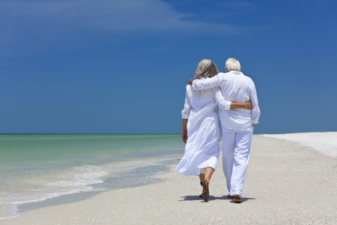 Older Couple Walking on Sandy Beach